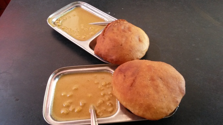 Sweet and leavened deep fried buns with a coconut gravy